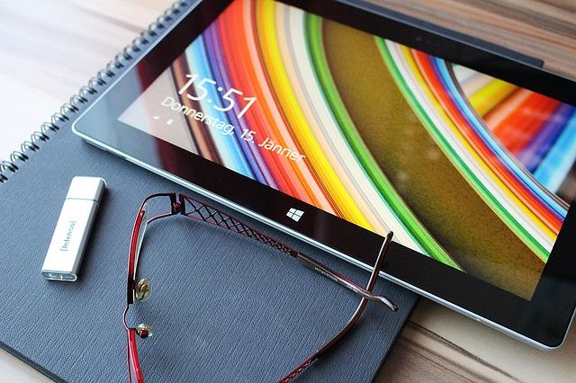 Tablet a USB flash disk ležící na zápisníku